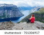 girl in red jacket sits on rock ... | Shutterstock . vector #701306917