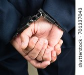 Small photo of close-up businessman hands in handcuffs. Businessman bribetaker or briber. Concept of fraud, detention, crime and bribery