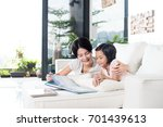 young asian mother reading a... | Shutterstock . vector #701439613