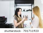 Small photo of Young pretty woman chosing color cosmetic and beauty consultant in shop or beauty salon