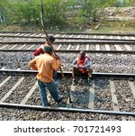 Small photo of AGRA - February 12, 2017: Indian train workers taking a rest on the train tracks. Repairing the fourth largest railway network in the world is of utmost importance for India