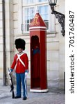 Small photo of The guards of honour in red galla uniform guarding the Royal residence Amalienborg Palace in Copenhagen, Denmark. Copenhagen, Denmark, April 16, 2010