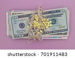 Small photo of Yellow pills on dollar banknote with rope bind on pink table, expensive healthcare concept