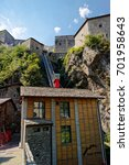 Small photo of Fort Bard, Valle d'Aosta, Italy - August 18, 2017: Wooden structure with diagonal panoramic elevator to climb the Fort Bard Historic Monument
