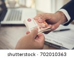 businessman giving money ... | Shutterstock . vector #702010363