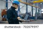 factory worker in a hard hat is ... | Shutterstock . vector #702079597