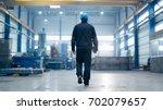 factory worker in a hard hat is ... | Shutterstock . vector #702079657