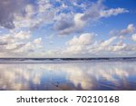 Blue sky and clouds reflected on a sandy beach - stock photo