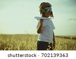 Small photo of Vacation, Boy playing to be airplane pilot, funny guy with aviator cap and glasses, carries in his hand a plane made of paper