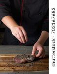 Small photo of Cooking raw beef steak with pepper and spices marinade on wooden table background by chef hands.