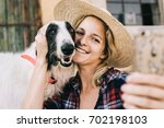 Small photo of Young woman taking self portrait wit her dog for social media profile picture