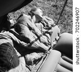 Small photo of Woman sleeping on an inflatable air mattress in tent