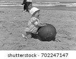 Small photo of Baby with good sense of humor with medicine ball on beach