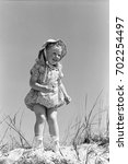 Small photo of Little girl in romper and matching sun hat standing on sand dune
