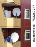 Small photo of Yellow and burgundy façade of a building in the German neighborhood of Kreuzberg, in Berlin. A flag of Palestine hangs from the satellite dish that carries the TV signal.
