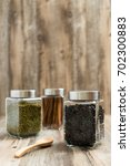 Small photo of Glass jar of black coffee bean altogether with green bean and cinnamon on wooden background.