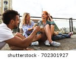 friends on rooftop party at... | Shutterstock . vector #702301927