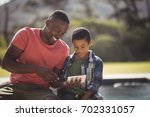 smiling son and father using... | Shutterstock . vector #702331057