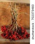 viburnum berries on the wooden... | Shutterstock . vector #702373483