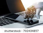 robot hand use mobile phone on... | Shutterstock . vector #702434857