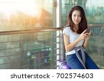 young girl asian traveler using ... | Shutterstock . vector #702574603
