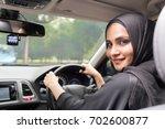 muslim women driving car. | Shutterstock . vector #702600877
