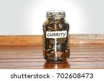 a glass jar full of coins to... | Shutterstock . vector #702608473