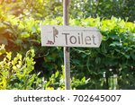 wooden sign toilet with nature... | Shutterstock . vector #702645007