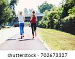 two young woman are jogging in... | Shutterstock . vector #702673327