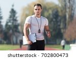 handsome personal trainer with... | Shutterstock . vector #702800473