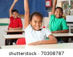 Three young school children arms raised in class - stock photo