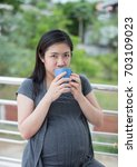 Small photo of Zooming closeup portrait of a beautiful young Asian woman dresses on grayish maternity cloth drinking juice in a blue cup to maintain her womb with blurry greenish bushes and trees as background
