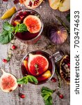 Small photo of Warming autumn, winter cocktail drink recipe. Hot red sangria with apples, plums, figs, pomegranate, mint, cinnamon, thyme, lemon. On dark stone table, with wooden cutting board, copy space top view