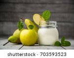 Small photo of Homemade natural farmer yoghurt for breakfast in jar with fresh fruits - pears and apples on wooden desk, top view
