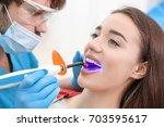 dentist doing procedure with... | Shutterstock . vector #703595617