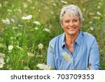 Stock photo happy attractive senior woman in a flower field in summer 703709353
