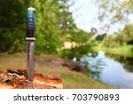 old hunting knife stuck in a... | Shutterstock . vector #703790893