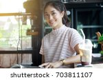 asian women smiling and reading ... | Shutterstock . vector #703811107