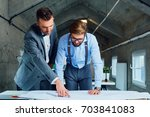 two architects looking at... | Shutterstock . vector #703841083