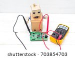 the robot holds a voltmeter in... | Shutterstock . vector #703854703