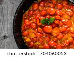 wok with fried tomatoes with... | Shutterstock . vector #704060053