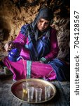 Small photo of Nomad Valley, Morocco - January 18, 2016: Nomad woman serving tea in the cave that is her home. Even now some Berber families are living traditional way.