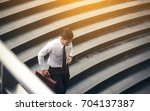 young asian businessman holding ... | Shutterstock . vector #704137387