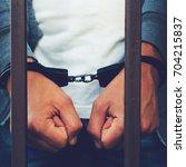 handcuffed hands of a... | Shutterstock . vector #704215837