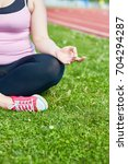 Small photo of Over-sized female in activewear sitting on green lawn with her legs crossed