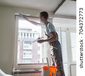 Small photo of Thirty years old manual worker with wall plastering tools inside a house. Plasterer renovating indoor walls and ceilings with float and plaster.