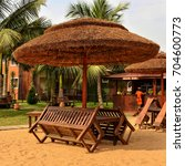 Small photo of Tropical thatched gazebo, benches, tables on a sand beach with buildings and open-air bar in the background. Travel and vacation. The Aqua Safari Resort. Ghana, Volta, Ada - January 14, 2017