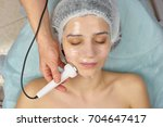 Small photo of Young woman undergoing phonophoresis. Girl in beauty clinic. Improving adsorptive properties of skin.