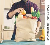 man examines a paper bag with... | Shutterstock . vector #704834923
