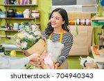 female florist offering flowers ... | Shutterstock . vector #704940343